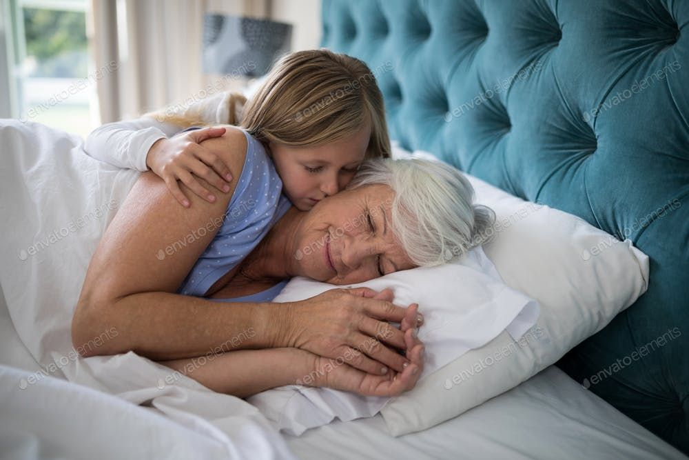 Granddaughter Kissing Her Grandmother On Bed By Wavebreakmedia S