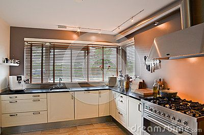 Cozinha moderna com fogão inoxidável e o assoalho de madeira