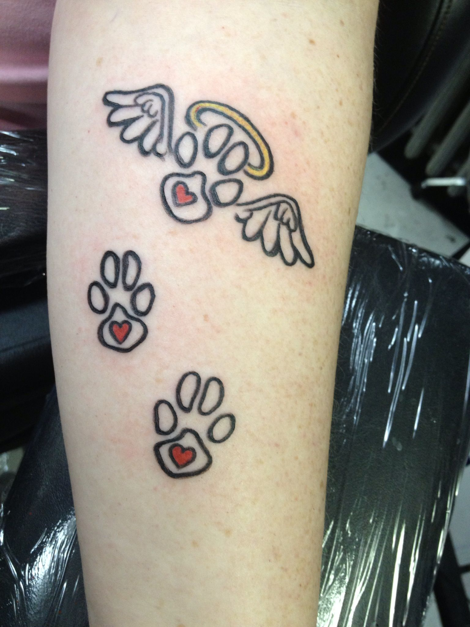 Paw print tattoos. Angel wings for each who has crossed over the rainbow bridge.