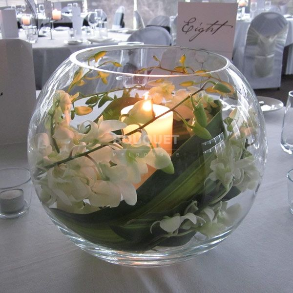 Fishbowl vase containing a swirl of white singapore