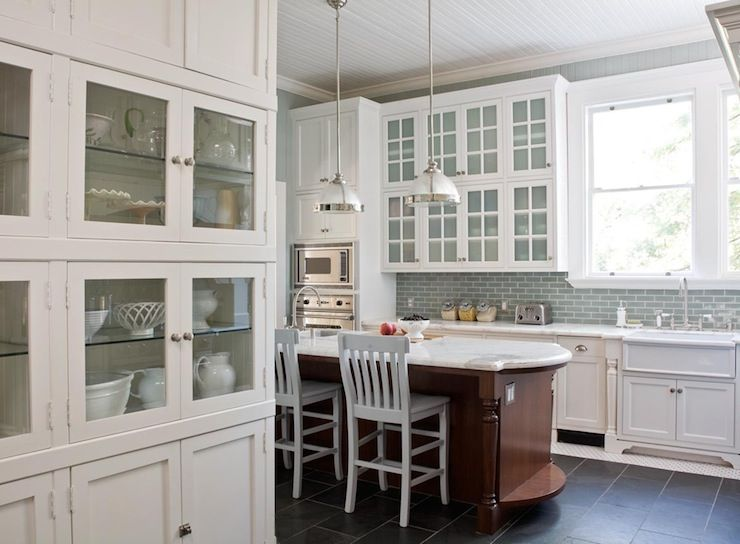 Two-tone kitchen with blue accents - Creamy white glass-front kitchen  cabinets,