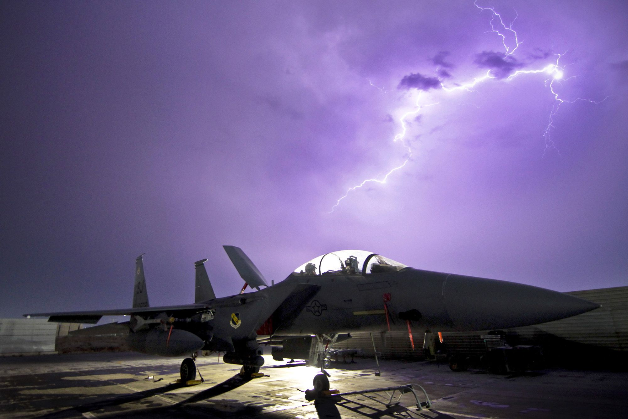 F15E Strike Eagle illuminated by lightning storm at