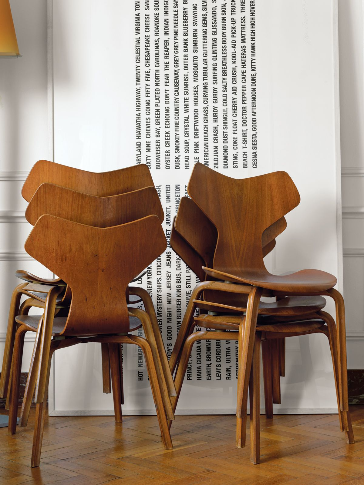 a stack of 1955 grand prix chairs by arne jacobsen rests besides a