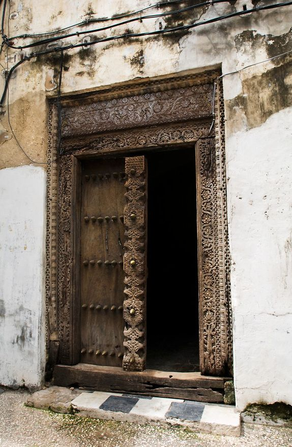 Old carved rustic historic doorway with brass detail and brass door knobs in Stone Town, Zanzibar, Tanzania, Africa. This doorway leads to a home, office or bureau.