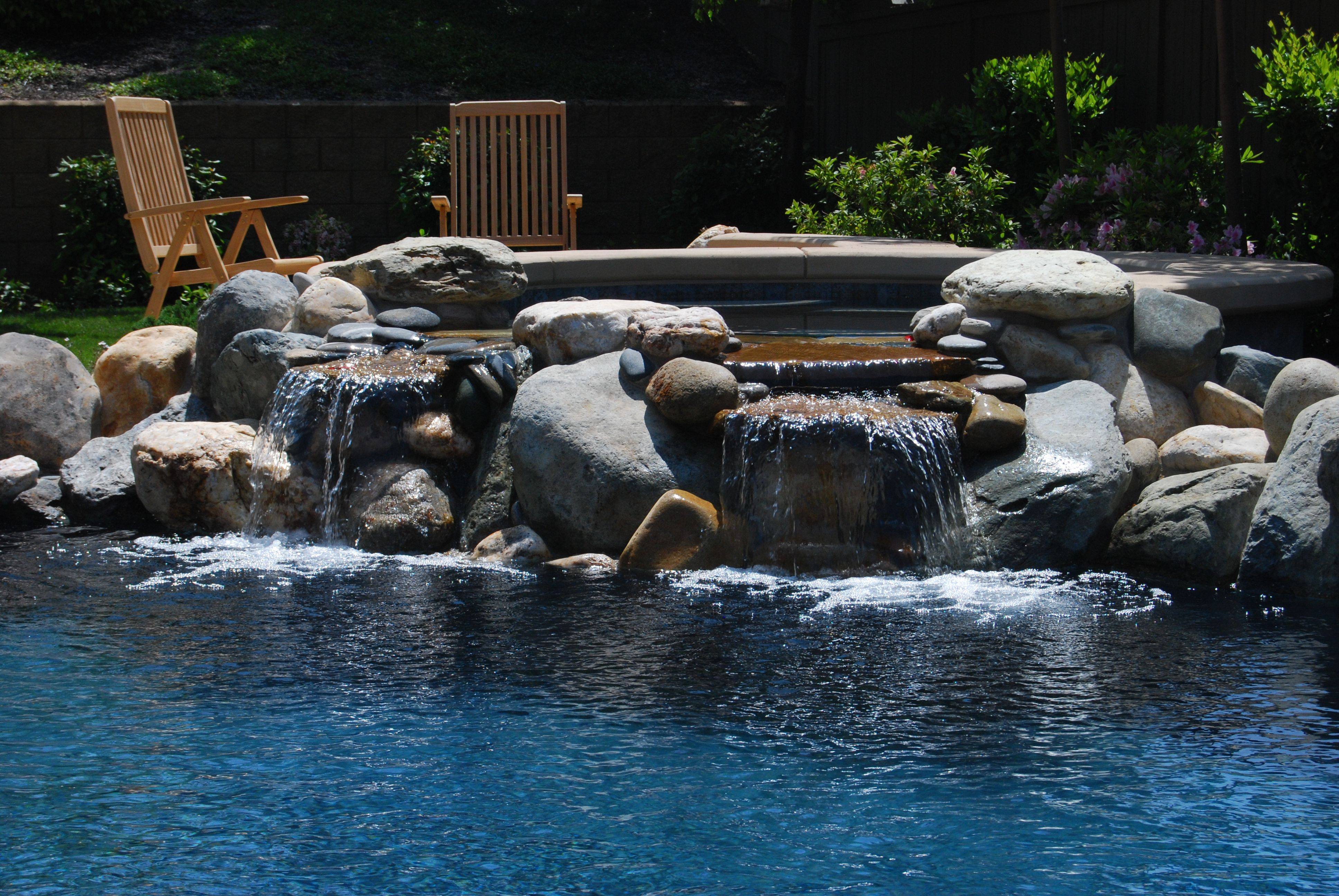 Natural Rock Waterfall Spilling From Raised Spa Pool Plaster Rock Waterfall Swimming Pools