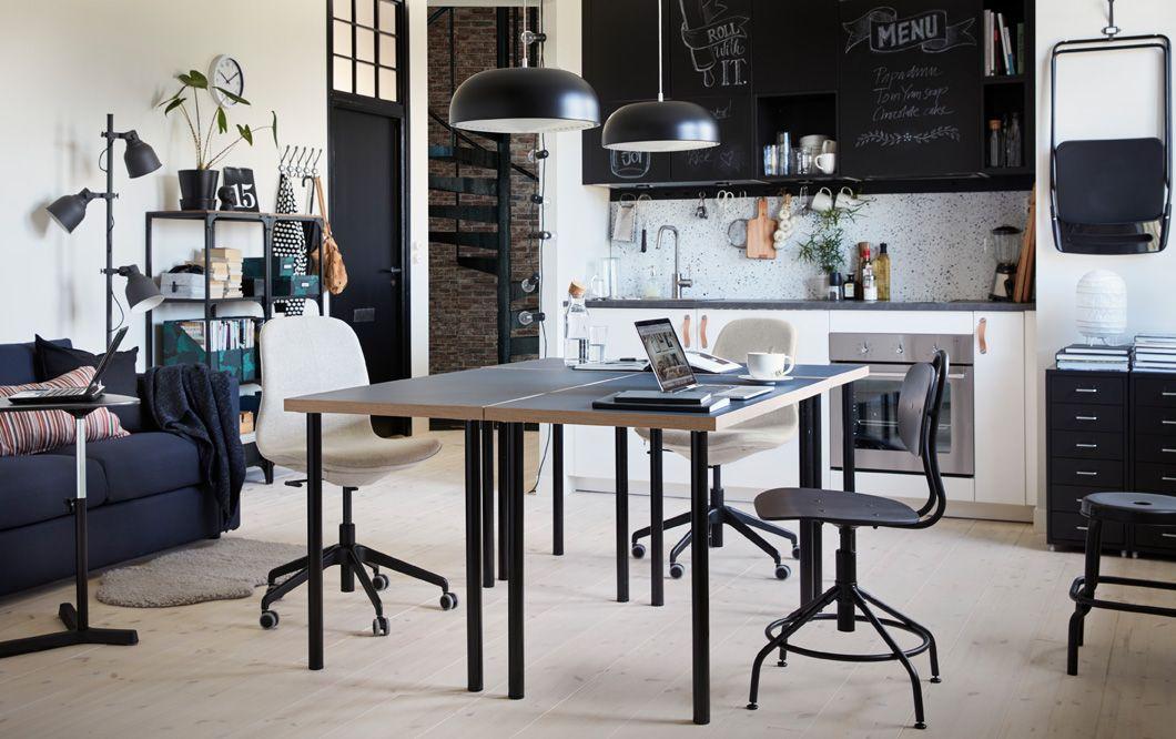 Cucina bianca e nera con due tavoli al centro della stanza, uno ...