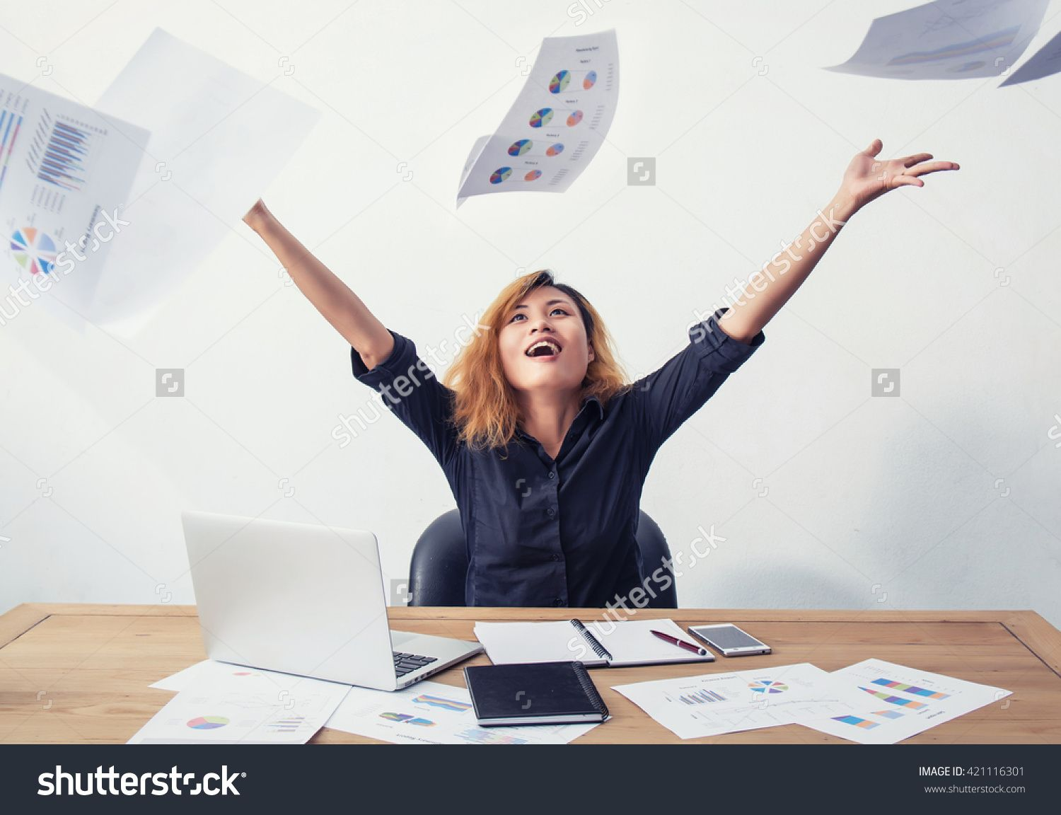 A Happy And Successful Business Woman With Her Arms Raised Working