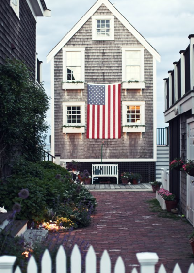 Large American Flag Hanging On The Side Of The House Beach