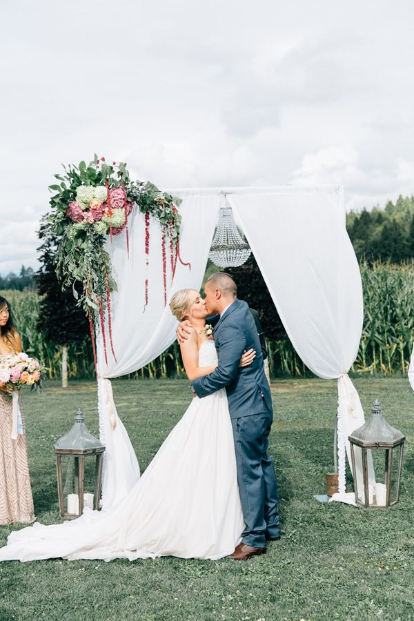 Fairytale Cottage Wedding at Craven Farm | draped ceremony backdrop with floral accent and lanterns | ceremony kiss - photo by Lora Grady Photography http://ruffledblog.com/fairytale-cottage-wedding-at-craven-farm