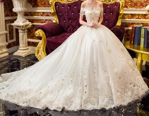 فستان زفاف أبيض بأكتاف منخفضة مزين بفصوص من الكرستال الذهبي متركز على منطقة الصدر ومتفرق على أنحاء الفستان تحت م Dresses Flower Girl Dresses Formal Dresses