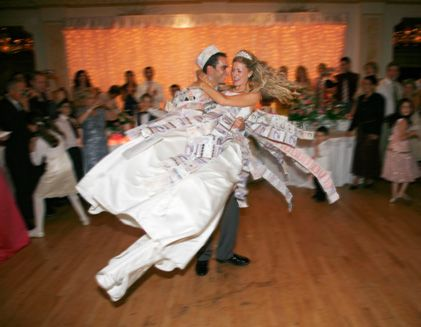 During The First Dance Guests Pin Money On Bride And Groom As A Gift