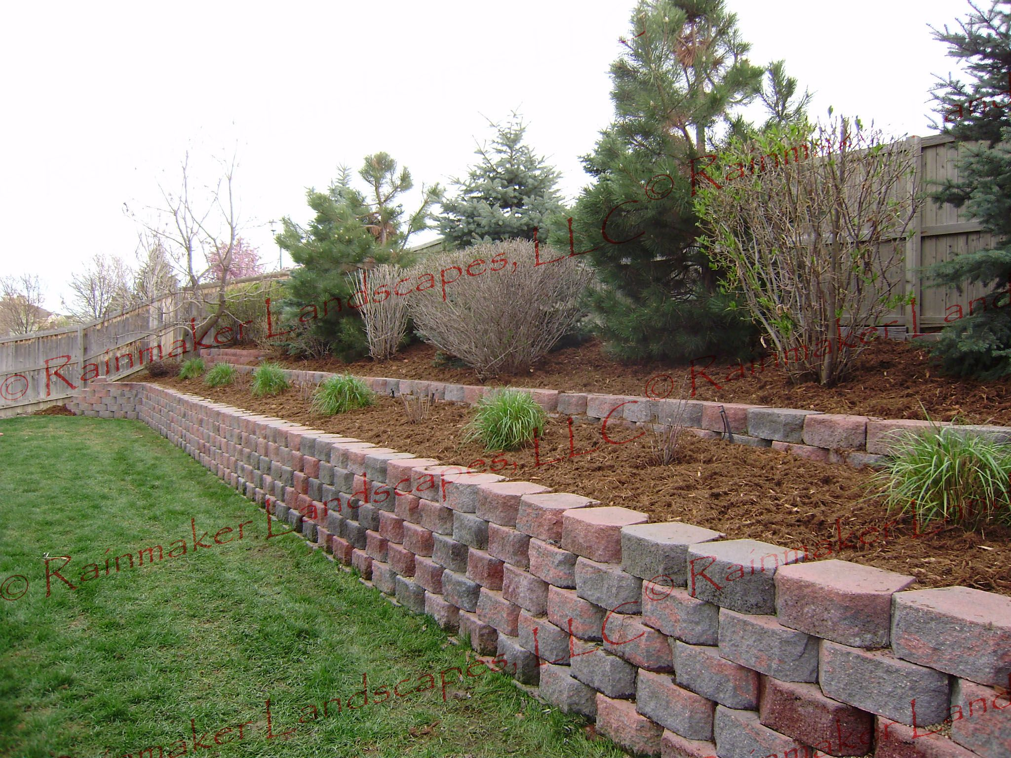 Double Tiered Retaining Wall With Trees And Shrubs Planted And