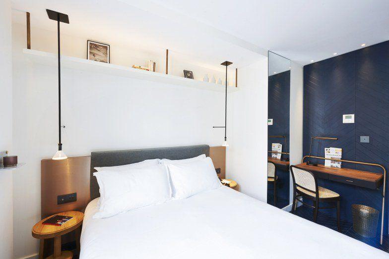 Um grande trunfo dos hotéis é o uso criativo de materiais comuns. Nesse dormitório do hotel parisiense Amastan, parquets azul-petróleo cobrem o chão e continuam em direção à parede, em projeto do Studio NOOC. O pé-direito alto é aproveitado por uma prateleira em nicho. A mistura de texturas e acabamentos valoriza a dimensão do espaço. Por $386 a noite.