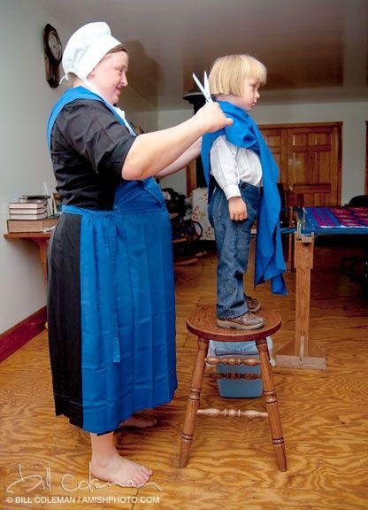 Senhora Amish cortando o cabelo ao filho.