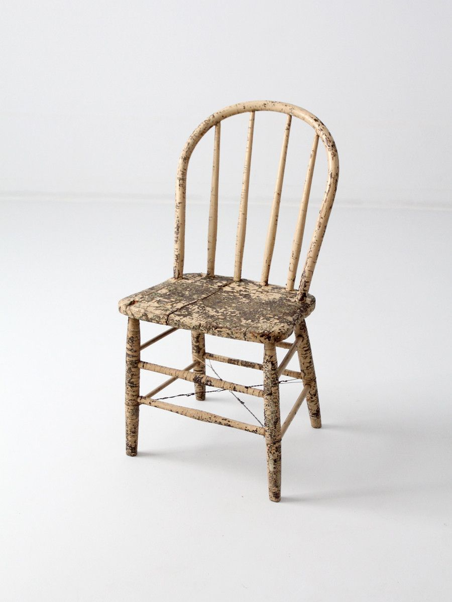 A 19th century antique spindle back chair. The primitive wood chair  features a bow back with spindles. Aged cream paint colors the chair. - Primitive Farmhouse Spindle Back Chair Circa 1800s New Business
