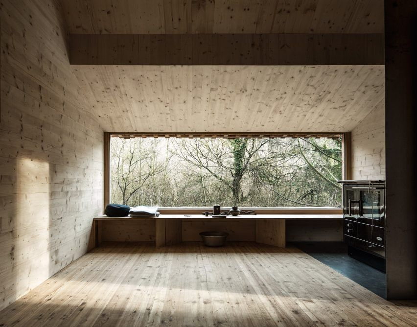 Shutters peel back from the front and rear facades of this cabin to open up large panoramic windows framing views into the woodland, while smaller openings are set in the sides.
