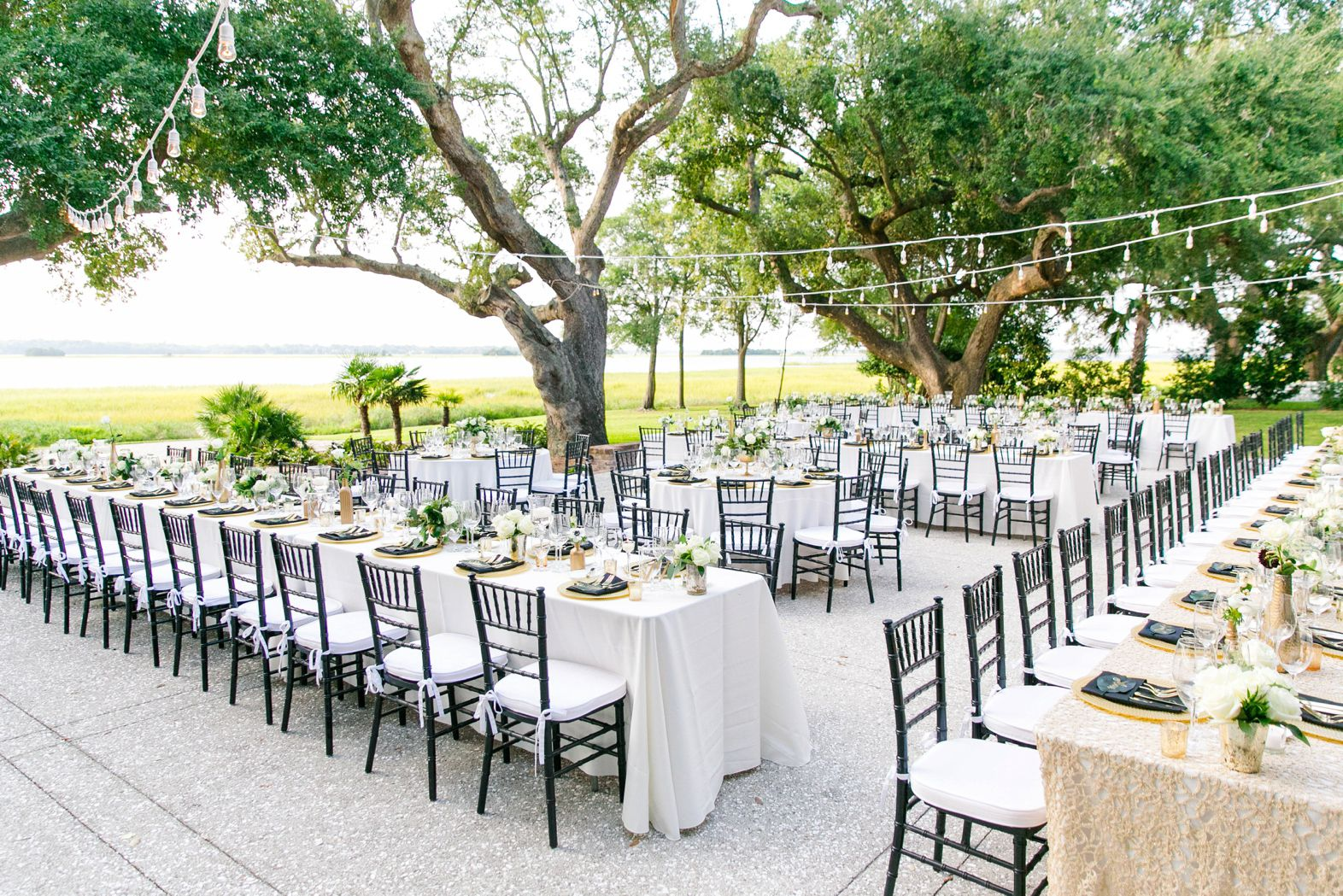 Black folding chairs wedding - Open Air Seating With Family Style Tables Gold Black White Green Lowndes