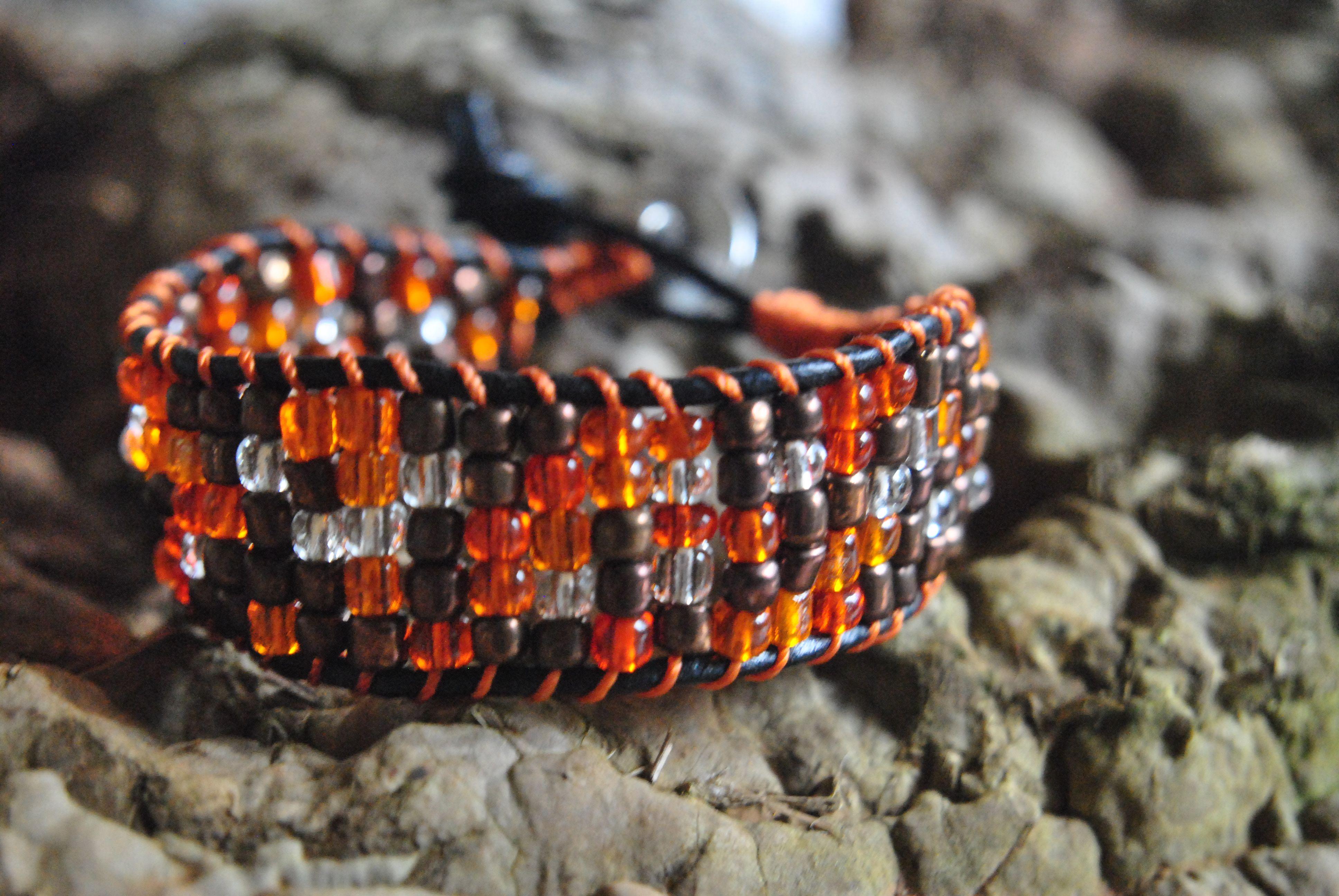 Ett armband knutet på läderband med oranga vita och kopparbruna pärlor..