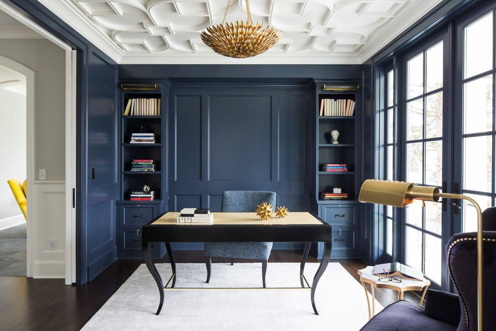 Navy blue office with custom built-ins, gold chandelier, and moulded