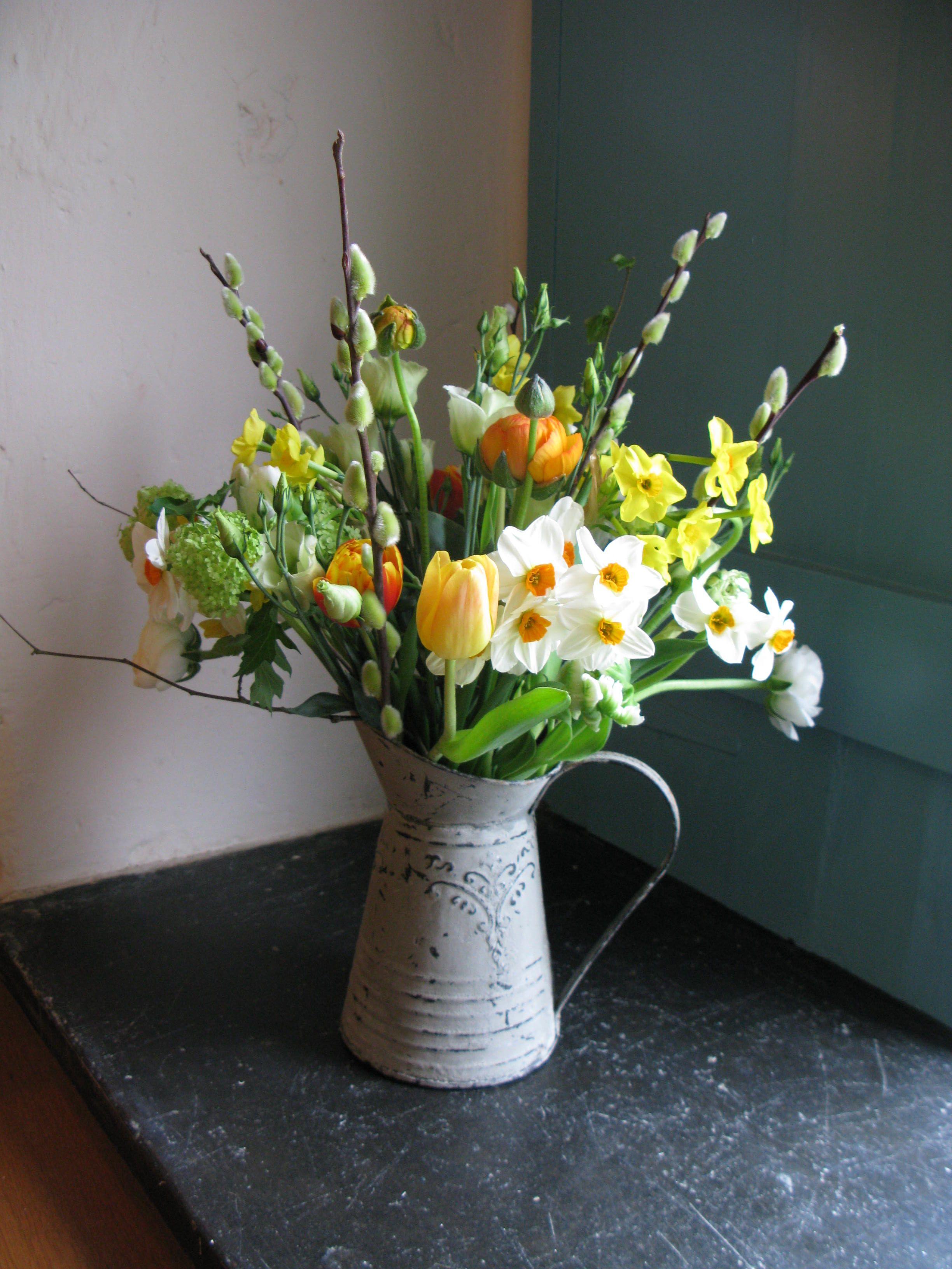 Rustic Metal Jugs Filled With Seasonal Spring Flowers In Oranges