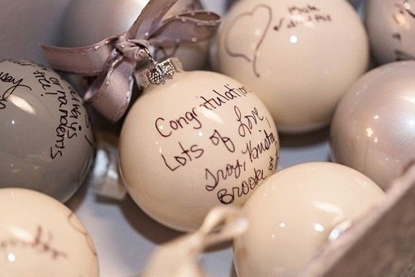 wedding guests sign ornaments for holiday guest book