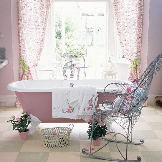 Gypsy bathroom Rose walls and a window framed by floral print curtains in magenta, lilac, lime and plum offset a pink-painted freestanding Fired Earth bath. The floral motif continues in cushions on a Garpa rocking chair and embroidered towels. A metal trellis basket holds hangers, roses in pots link the garden. Warm Marmoleum tiles in sage and cream add subtle colour.