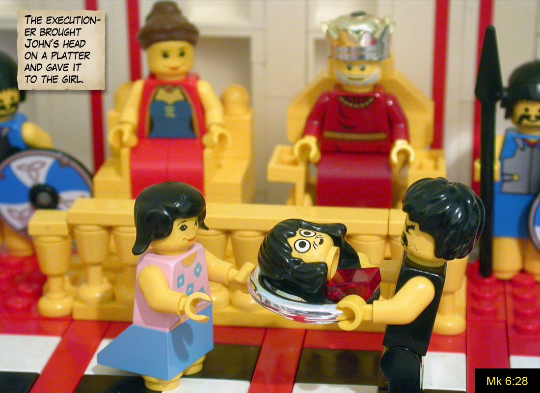 """ID: legos depict the scene of John's head being presented to Herod's daughter, Herodias.  In the upper right, a scroll reads """"The executioner brought John's head on a platter and gave it to the girl."""""""