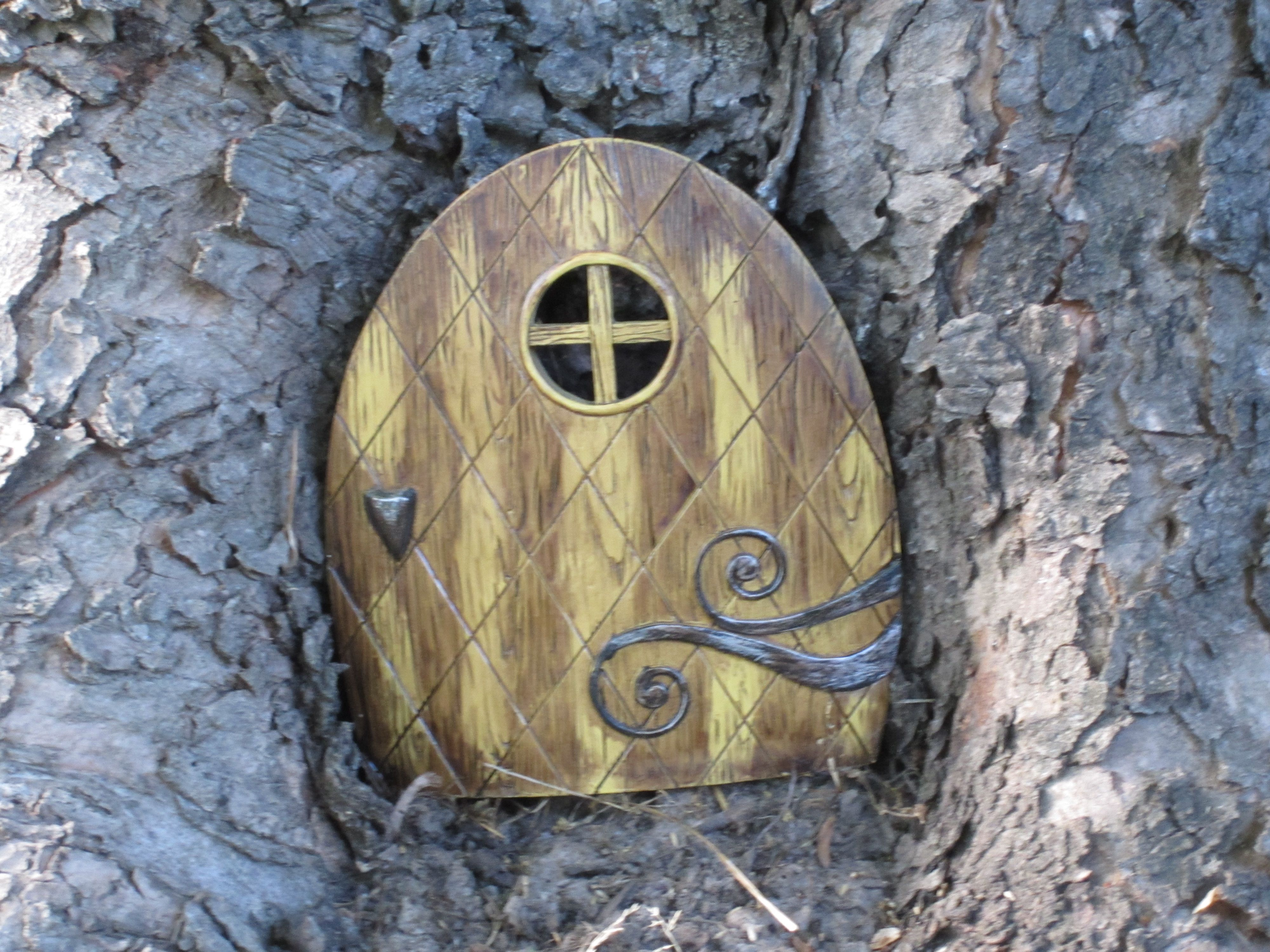 A friend got me this little elf door. It just fits in one of the nooks at the base of my old maple.