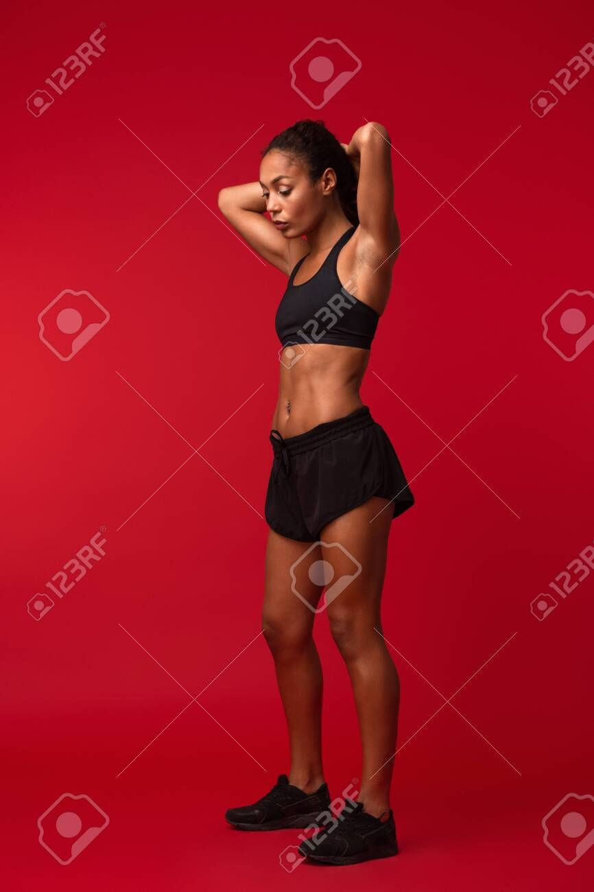 Image of a beautiful young african sports fitness woman posing isolated over red wall background. ,...