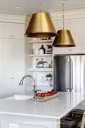 Photo of This white transitional kitchen cleverly mixes multiple metals: stainless steel#…