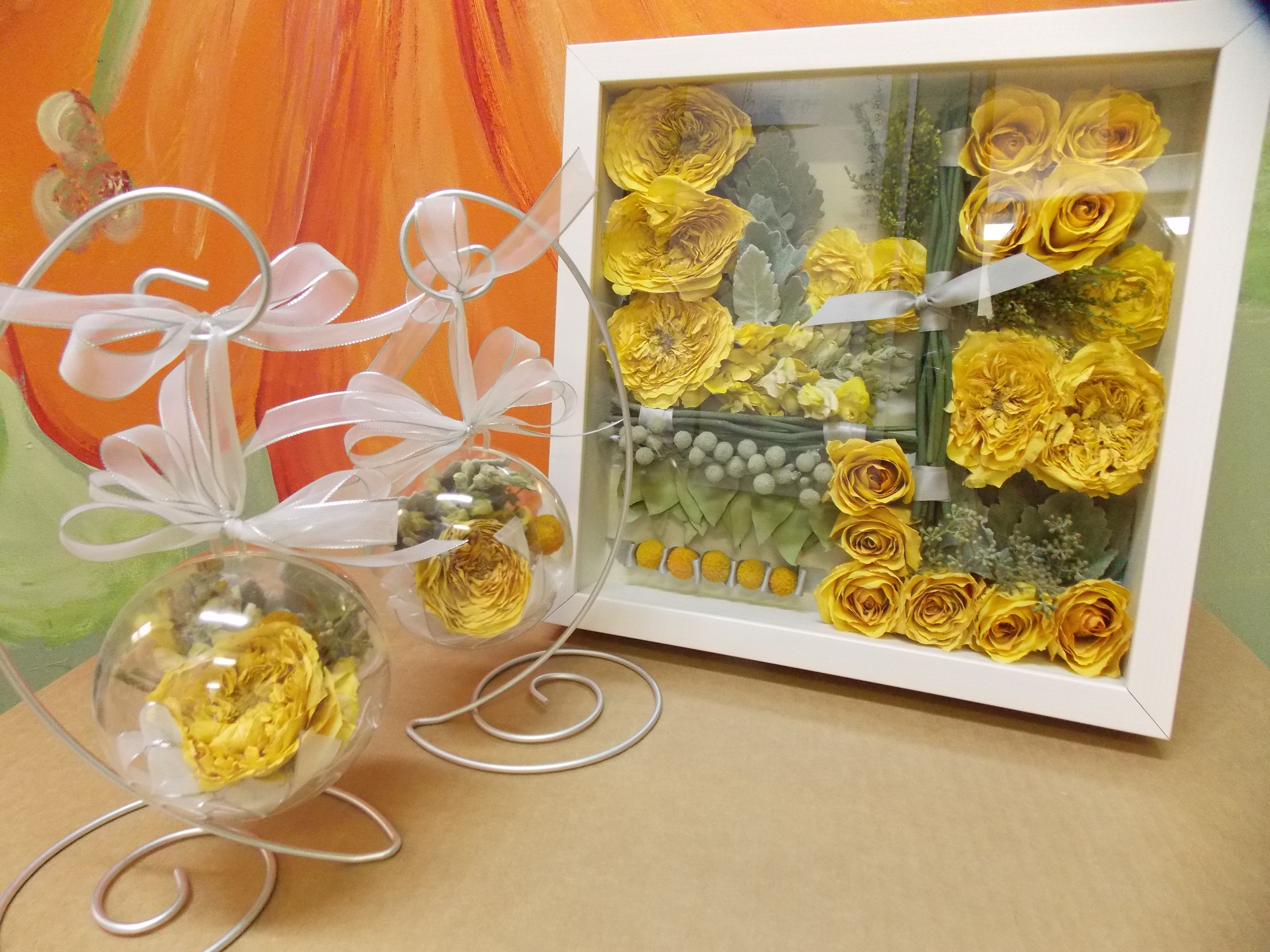 Happy Yellow dispersed among three keepsakes!  The bride's bouquet preserved for her in the white shadowbox and in two acrylic ornaments for family members.
