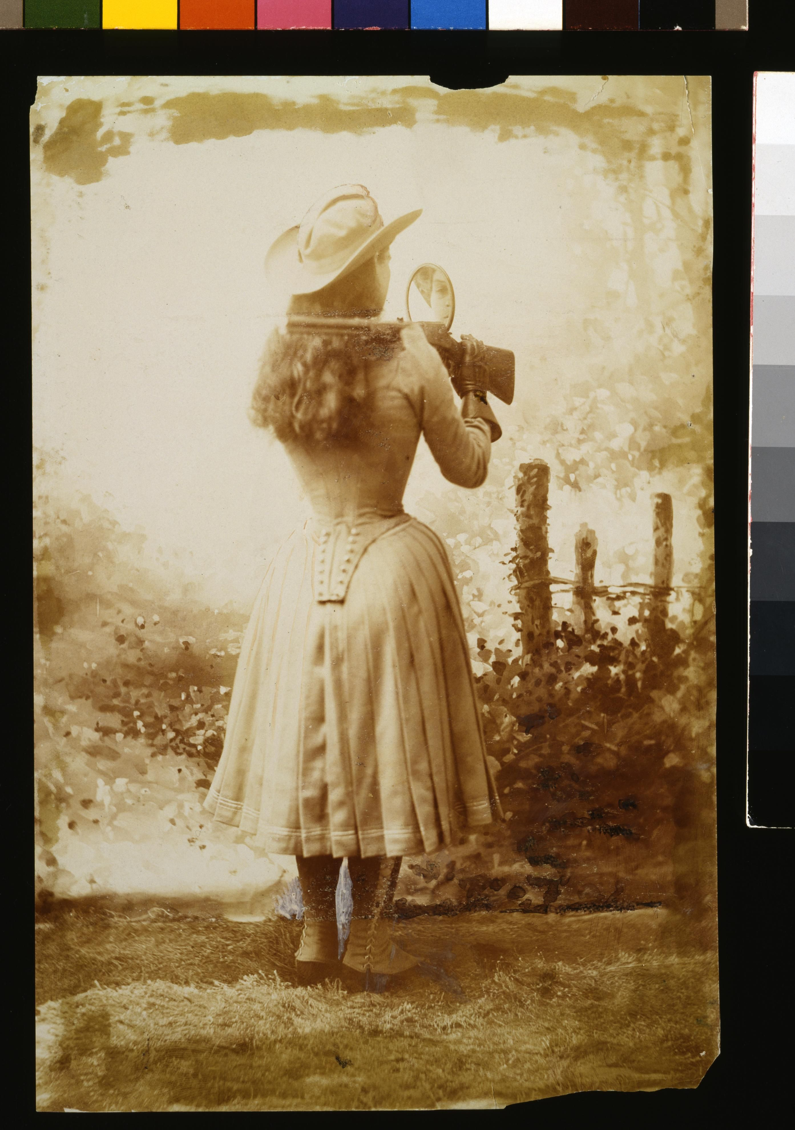Annie Oakley demonstrates her skill by shooting backwards