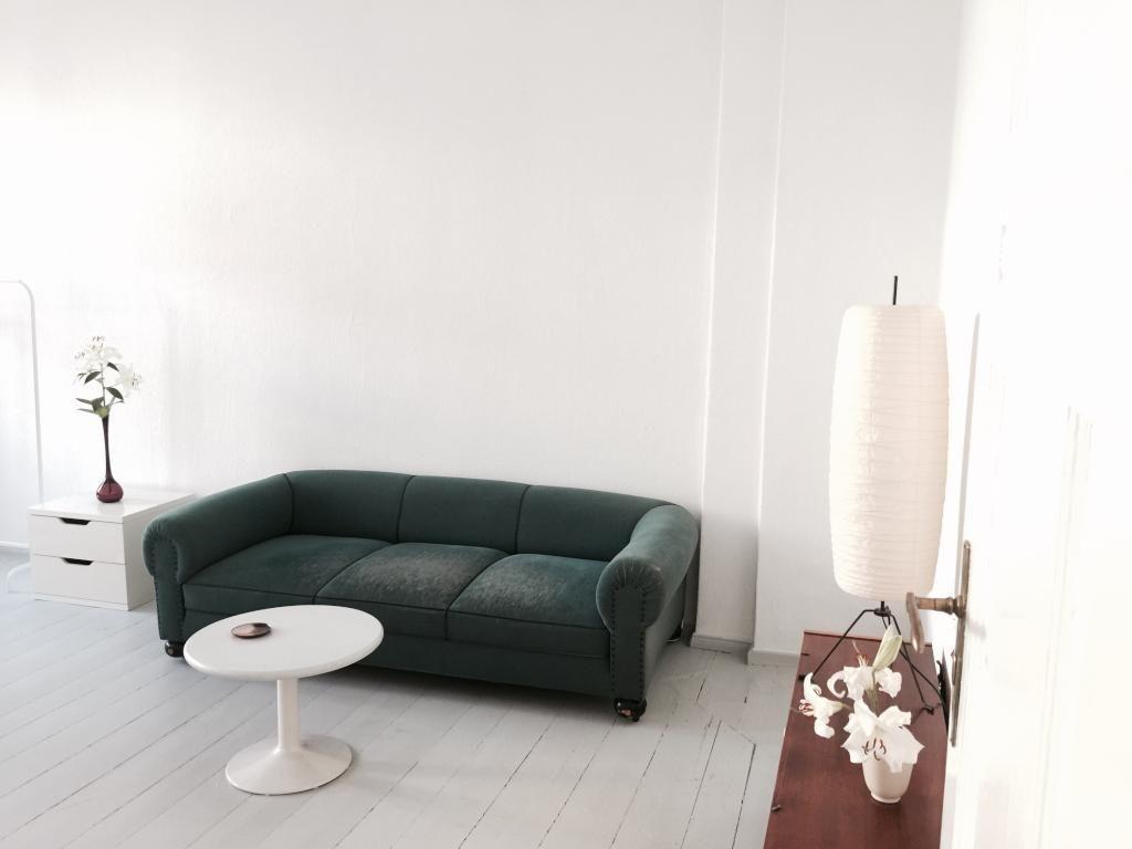 Schönes Helles Wohnzimmer Mit Weißen Dielen Und Dunkler Couch, Weißem Couch Tisch  Und Brauner
