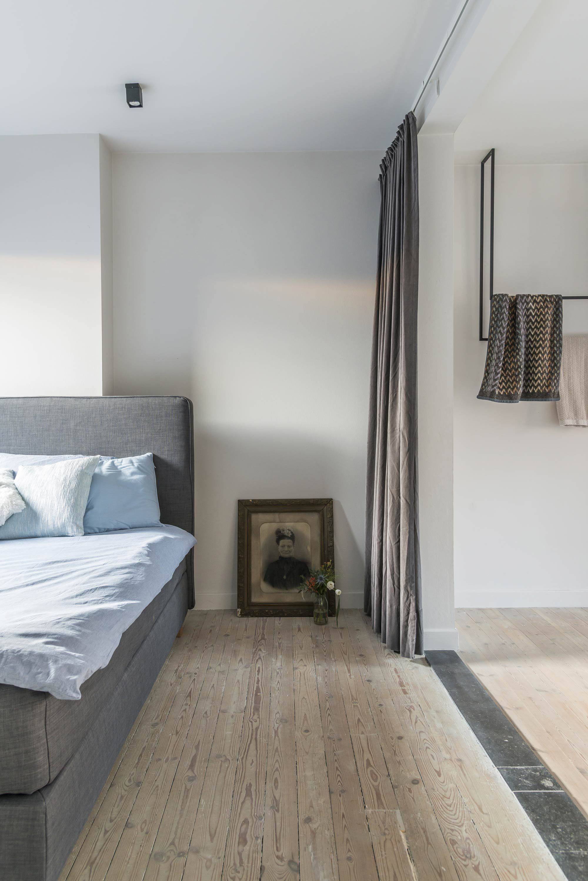 Slaapkamer met grijs bed en houten vloer | Bedroom with grey bed and ...