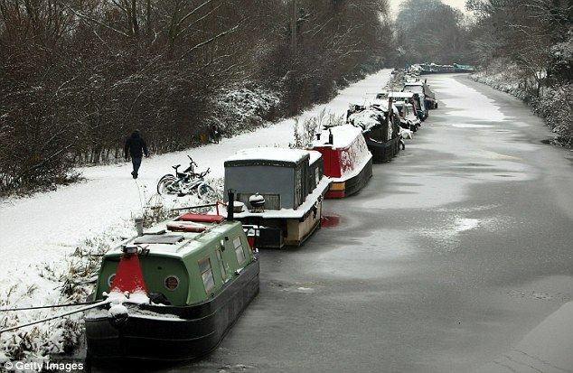 Snow gathers on canal boats moored along the frozen Kennet and Avon Canal in Bath