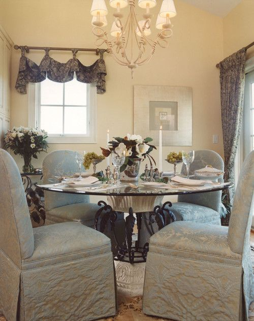 A Round Glass Dining Table Blue Classic Chairs Printed Window Treatments And A Chandeli Glass Round Dining Table Transitional Dining Room Dining Room Design