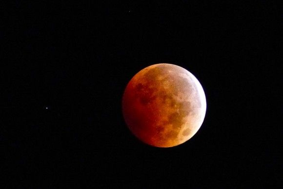Lunar eclipse on the night of October 8, 2014.  The object to the left is the planet Uranus!  This beautiful photo is by Janey Wing Kenyon of Story, Wyoming.