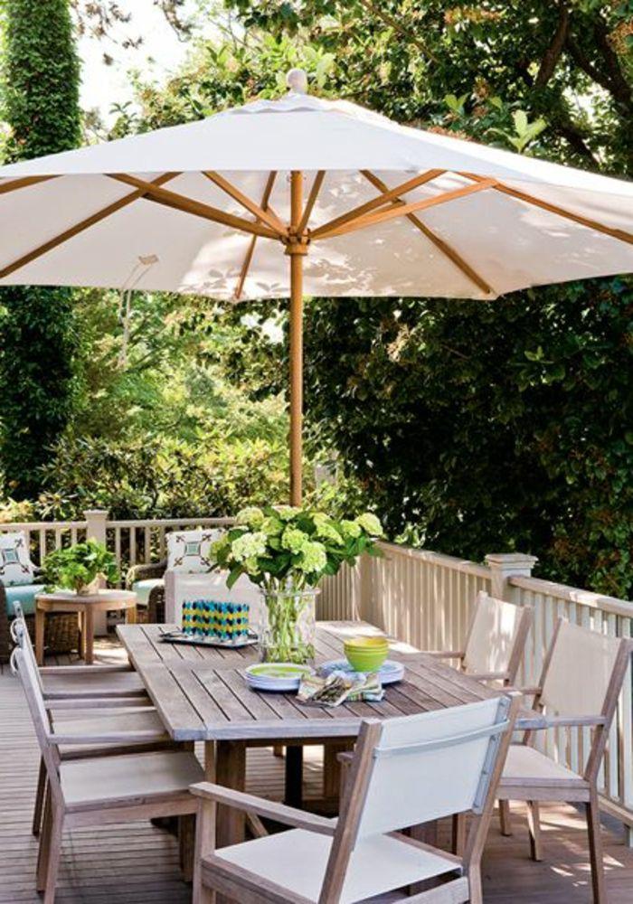 une jolie terrasse avec parasol de jardin blanc, parasol en bois et
