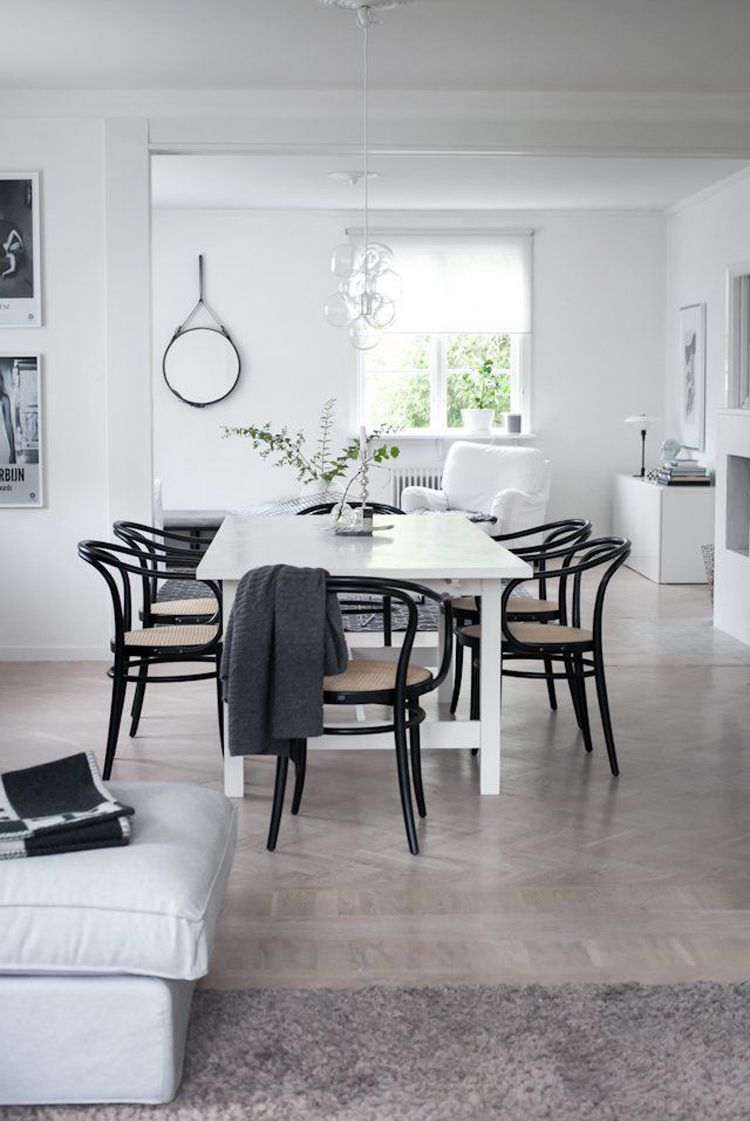 Black bentwood chairs around white dining table
