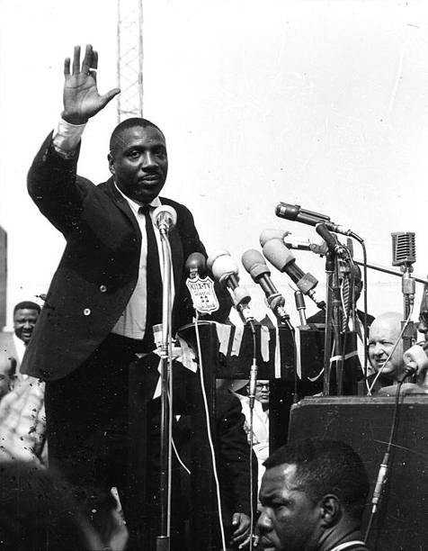 Photo of activist Dick Gregory waving to the crowd assembled to hear Dr Martin Luther King Jr at Wrigley Field in Los Angeles May