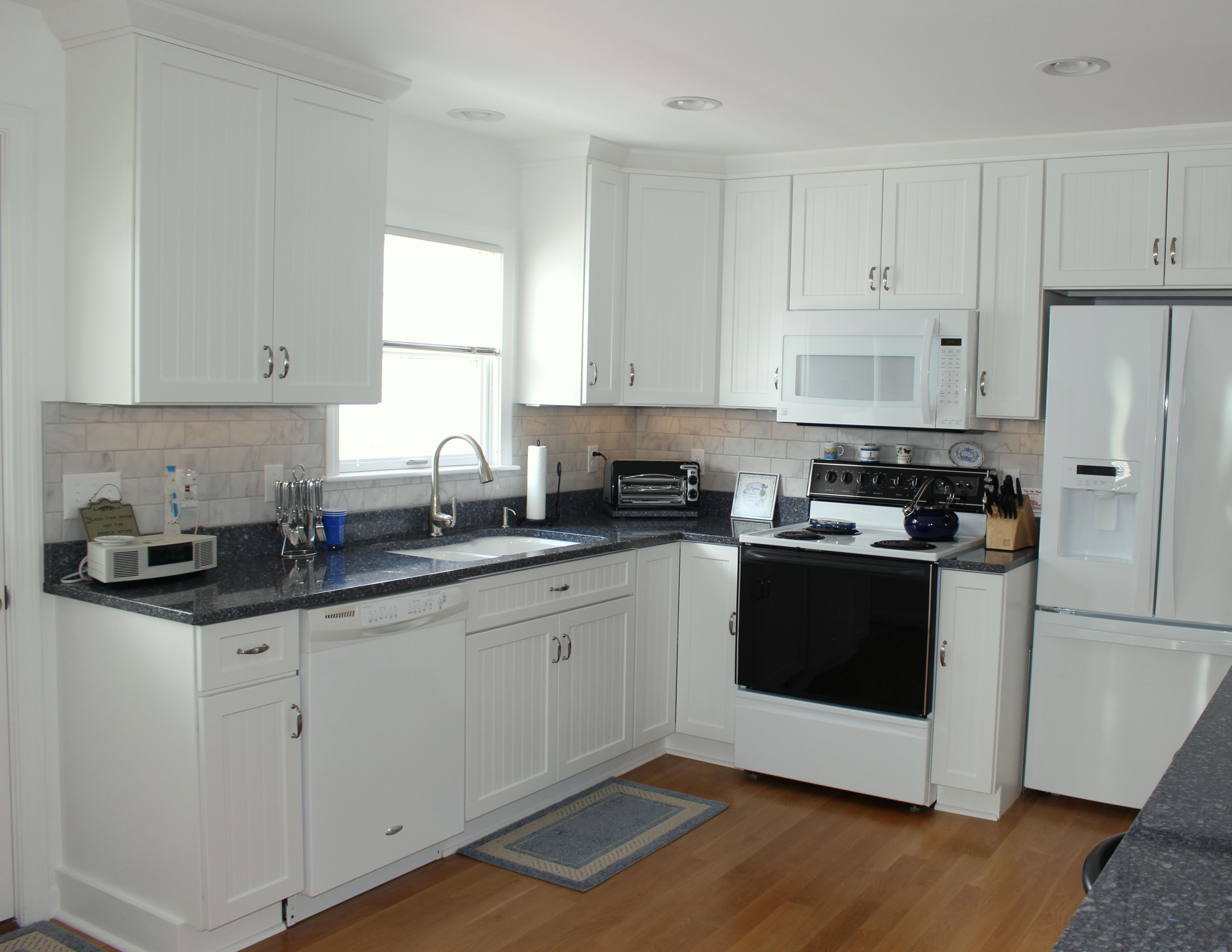 The Color Palette Of The Beach Sand And Ocean Waters Are Carried Inside To The Kitchen With The White Kitchen Renovation Bead Board Cabinets Stone Countertops