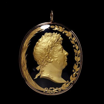 This pendant was created in 1814 as a gift for Sir William Knighton, physician to the Prince of Wales (the Prince Regent, later King George IIV).    The inclusion of the attributes of peace (olive) and victory (palm) in the design (marking the successful outcome of the wars against Napoleon) suggest an 1814 creation for the pendant which also features a portrait head of the Prince of Wales with a laurel wreath.