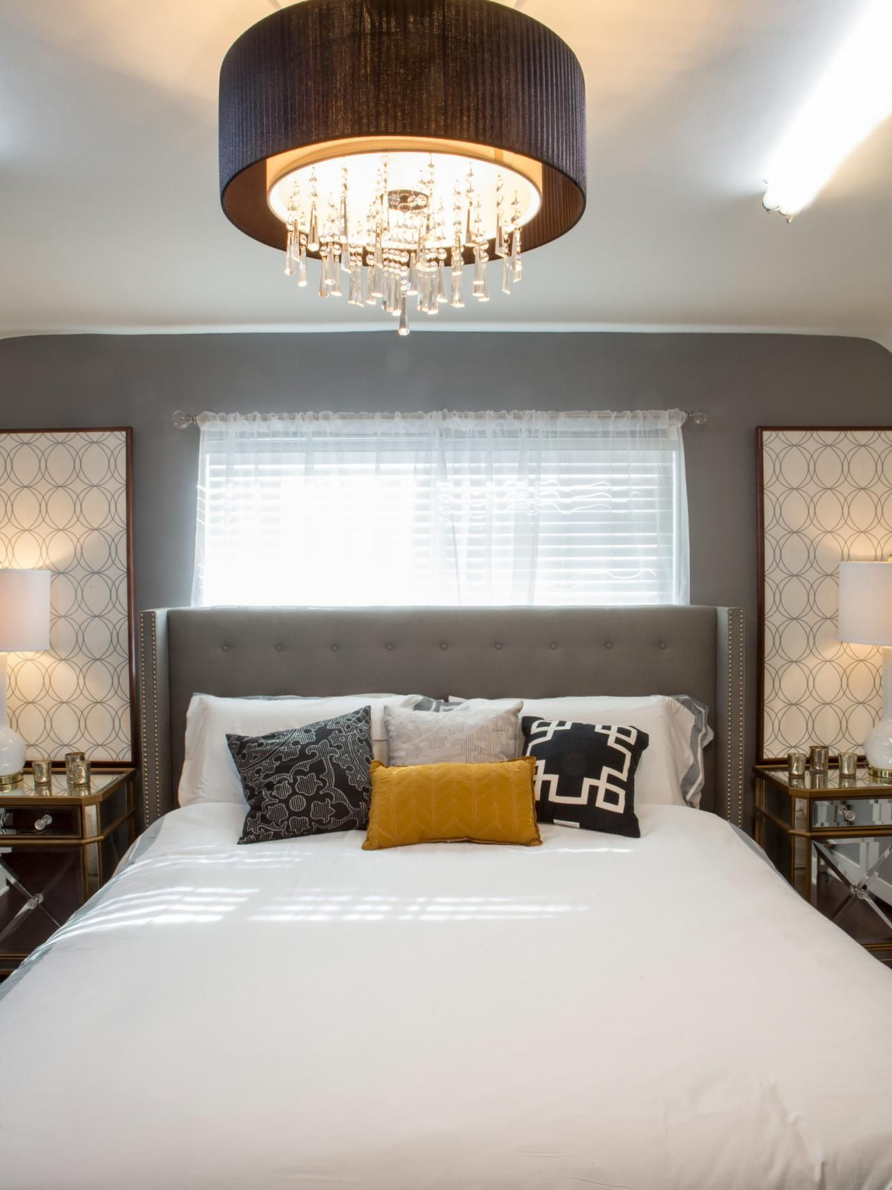 This bedroom gets a sophisticated look from midcentury modern furnishings. The focal point of the room is a large circular drum ceiling light with dangling prisms that shines light on the bed with a nail head upholstered headboard.