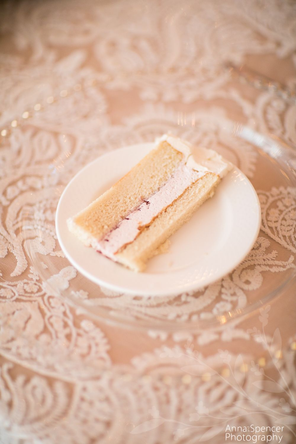 Slice of white wedding cake with strawberry filling on a pink lace ...