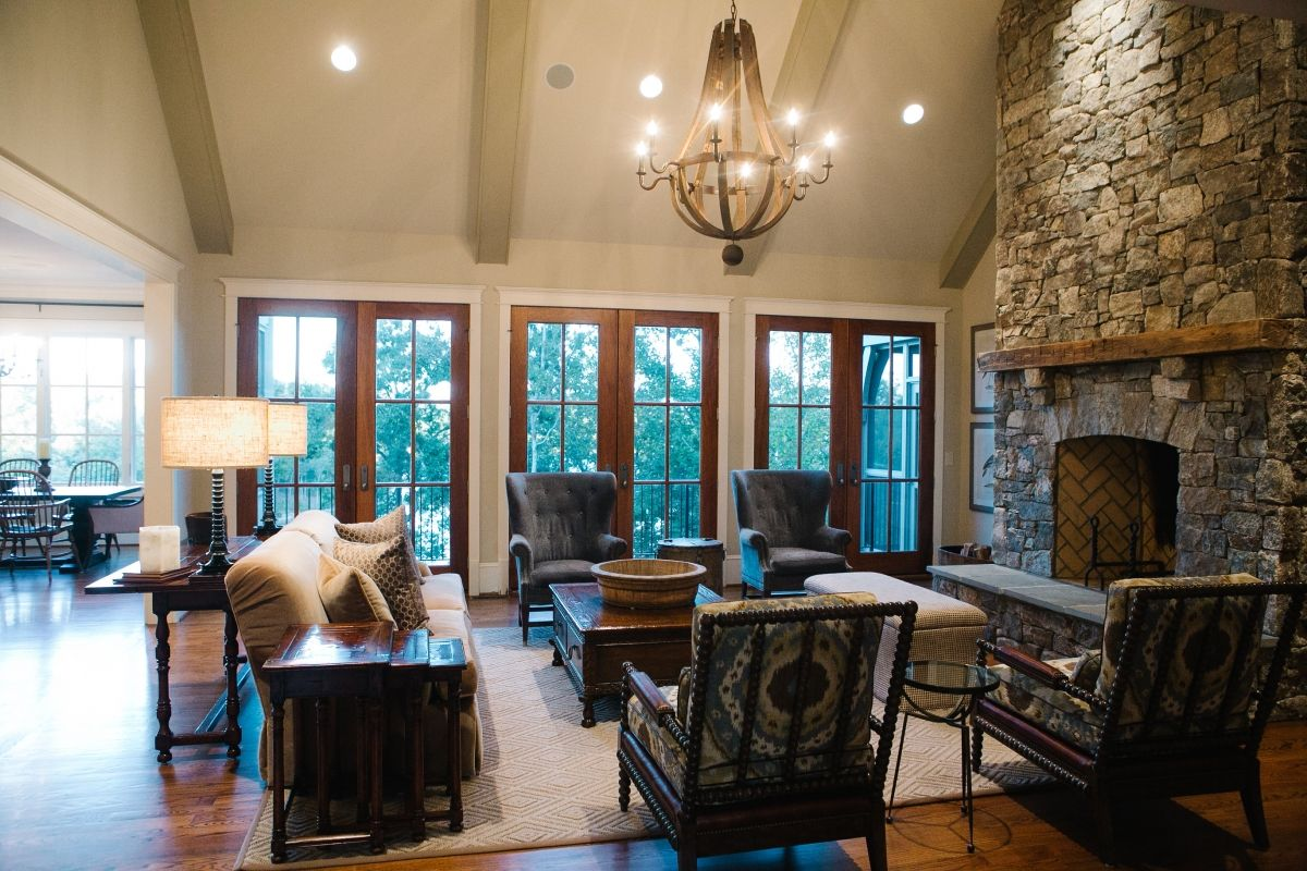 Beautifully Styled Living Room French Doors Overlooking Lake Keowee Cathedral Ceiling Exposed Beams French Doors Farm House Living Room Custom Home Builders Living room french doors