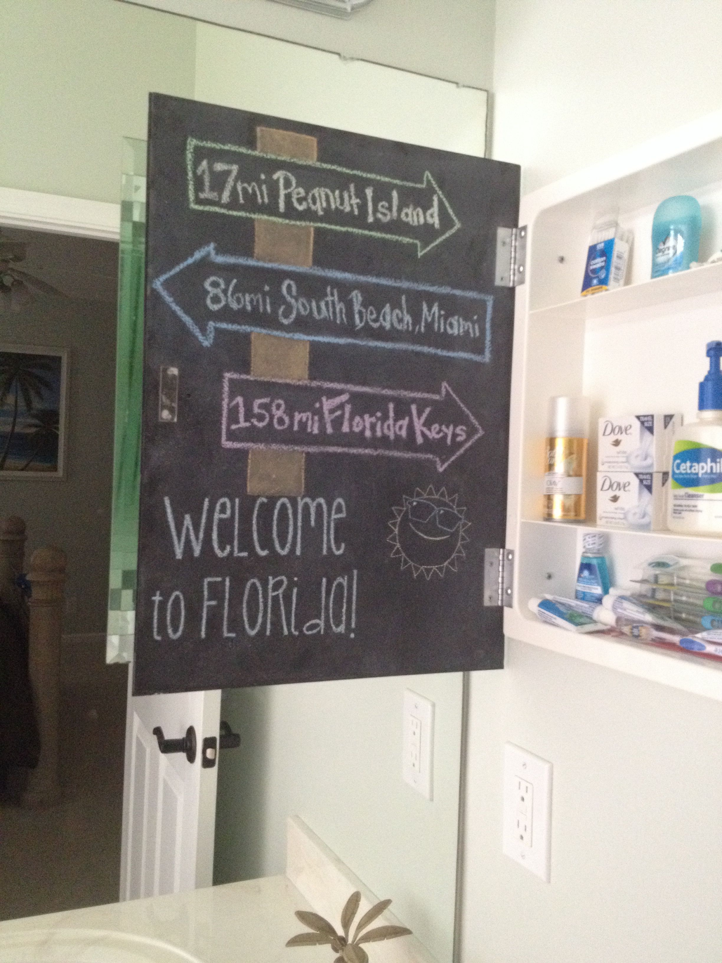 Welcome chalkboard inside medicine cabinet in guest bathroom with toiletries for guests
