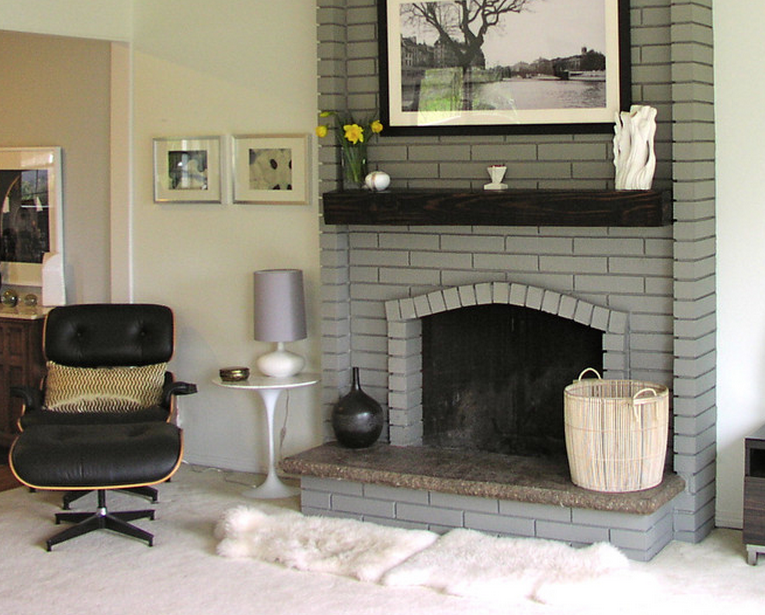Painted brick fireplace in a light gray with dark wood mantel in a