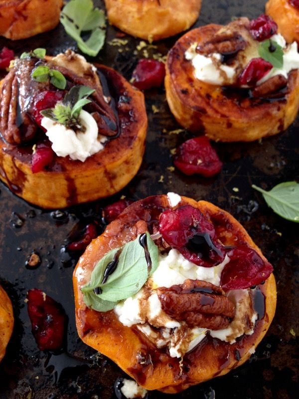 A Festive Appetizer of Sweet Potato Rounds with Goat Cheese, Cranberries & Honey Balsamic Glaze, finished with a blood orange infused olive oil and fresh basil!