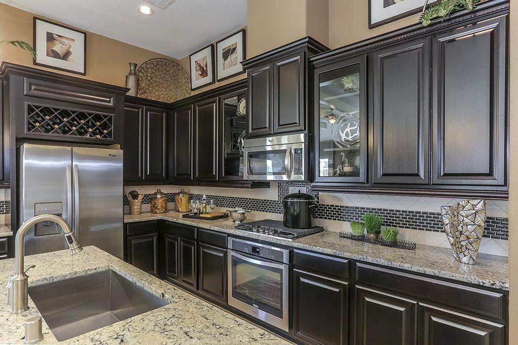 Gehan Homes Kitchen Dark Wood Cabinets Wine Wrack Stainless Steel Appliances Glass Best Kitchen Countertops Dark Grey Kitchen Cabinets Trendy Kitchen Tile