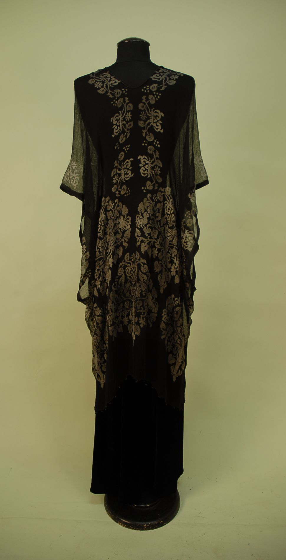 Back View STENCILLED BLACK SILK GAUZE TUNIC, 1920's. Probably Gallenga, square cut wrap with silver Renaissance style trees and stylized creatures, black Venetian glass beads along hem, knotted cord closure with glass bead tassels. 32 x 33.